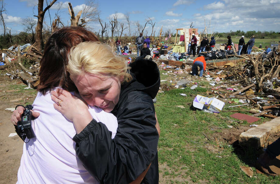 Sara Shogren, left, is hugged by Zoey Patrick as friends sort through the rubble of Patrick's home, Sunday, April 15, 2012, in Marquette, Kan. Photo: Tom Dorsey, Associated Press / Salina Journal