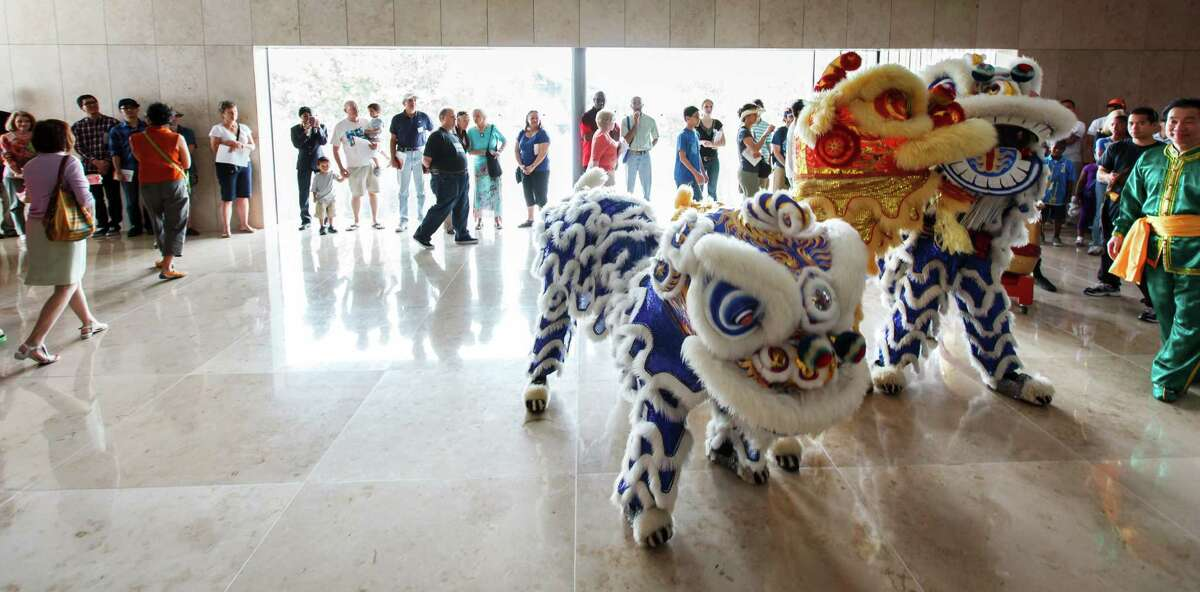Members of Lee's Golden Dragon troupe perform a traditional Chinese lion dance Sunday near the reflecting pool at the Asia Society Texas Center during the First Look Festival.