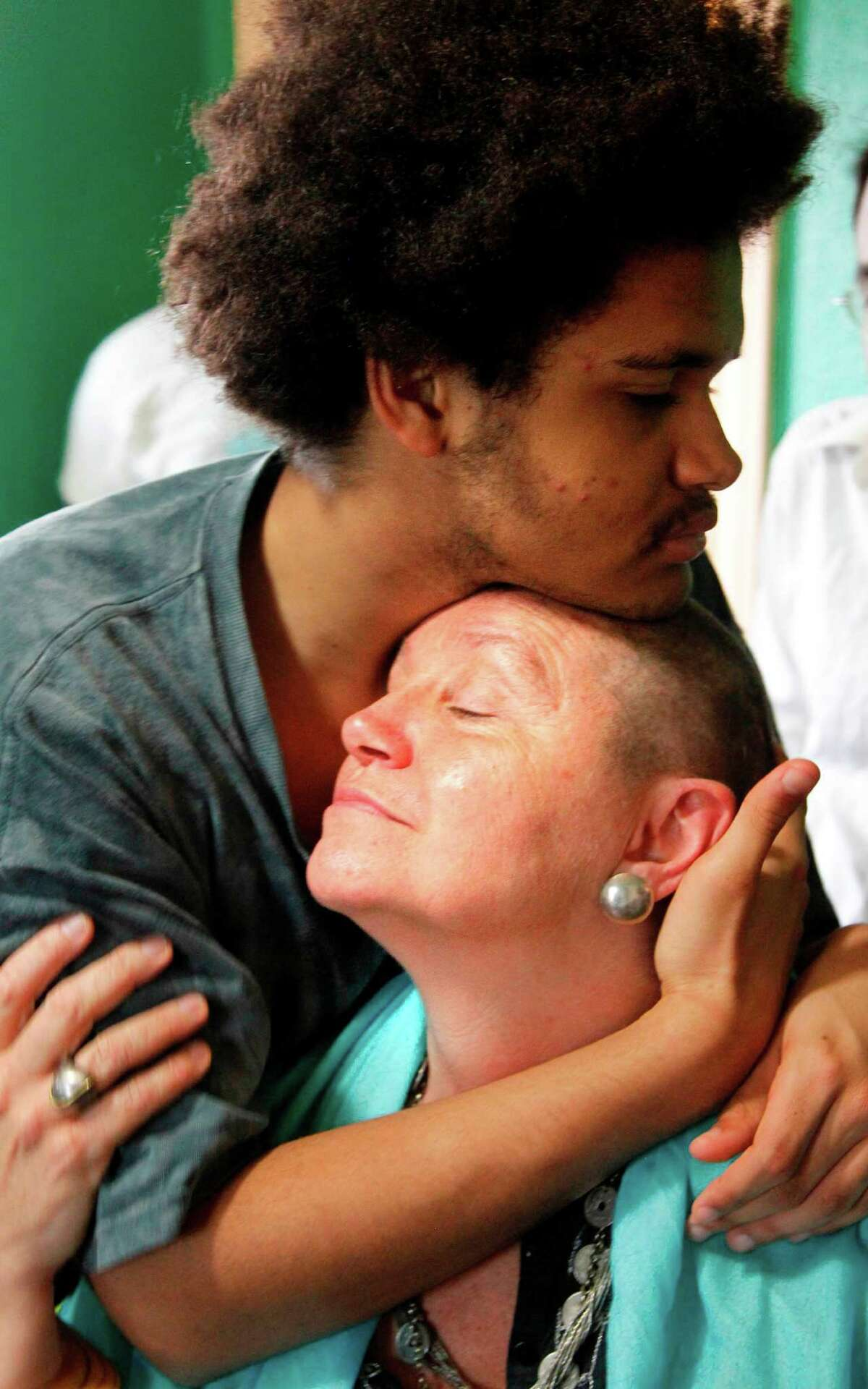Son Isaac Taylor, left, embraces Stowe, a pediatrician, after her hair is cut off late last month at the Alliance for Cooperative Transformation in Houston.