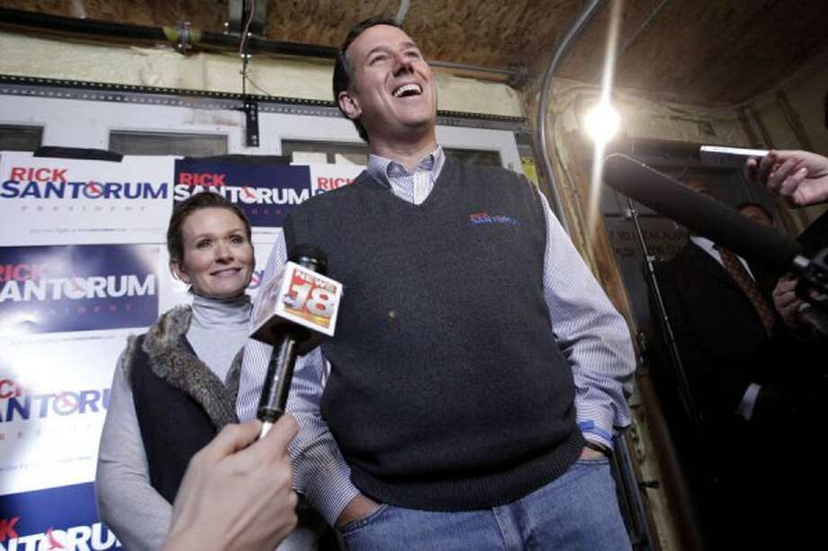 Republican presidential candidate, former Pennsylvania Sen. Rick Santorum, center, talks to wife as he is joined by his wife Karen after a campaign stop in Chippewa Falls, Wis., Friday, March 30, 2012. (AP Photo/Jae C. Hong) (Associated Press)