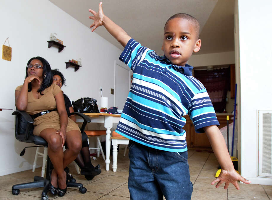 Isaiah Nicholas, 4, dances for his mom, Rosharon Ceasar, left, and grandma Lisa Ceasar on Sunday. He was shot in the head two weeks ago and was on life support for several days. He was released from the hospital last week. The entry wound is between his eyes. Photo: Cody Duty / © 2011 Houston Chronicle