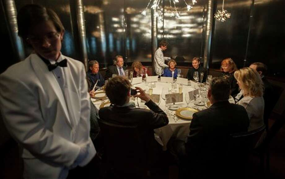 Servers Zack Black, left, and Evan Boyle, center, tend to guests during a re-creation of the final first class dinner served on the RMS Titanic, Saturday, April 14, 2012, in Houston. The Titanic sank in the North Atlantic Ocean April 15, 1912 after colliding with an iceberg during her maiden voyage from Southampton, England to New York. Photo: Dave Einsel, AP / FR43584 AP