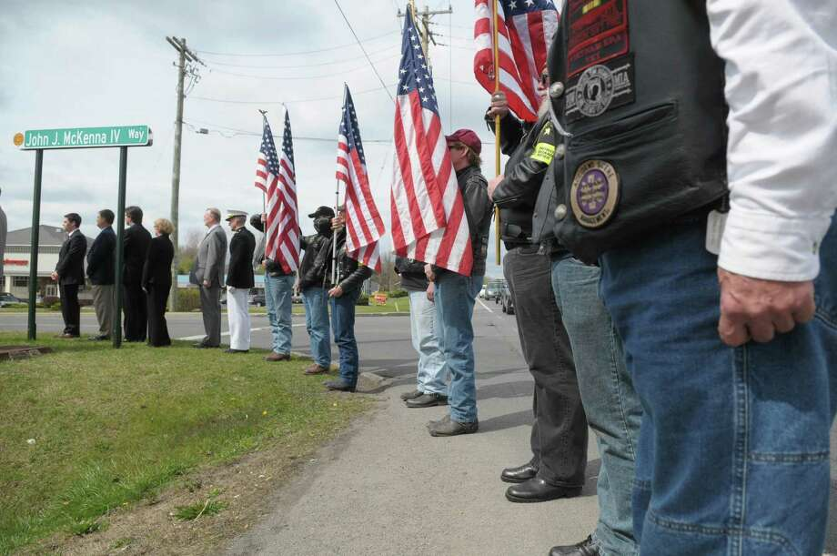 Members of the Patriot Guard Riders hold flags  during a ceremony for the naming of the street John J. McKenna IV Way on Sunday, April 15, 2012 in Clifton Park, NY.  John J. McKenna IV was a Clifton Park native and a New York State Trooper.  McKenna serving with the military when he was killed in action on August 16, 2006 in Fallujah, Iraq.  (Paul Buckowski / Times Union) Photo: Paul Buckowski