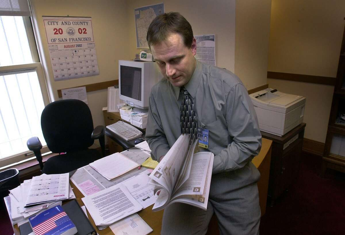 San Francisco voters can now opt out of receiving the paper copy of the Voter Information Pamphlet in the mail. VOTE-C-14AUG02-MN-PG John Arntz, acting dir. at Dept of elections in SF, thumbs thru a voter information pamphlet from the year 2000 which is over 200 pages long. He is concerned about the one coming out soon which will be over 300 pages and cost alot if mailed. San Francisco Chronicle PHOTO BY PENNI GLADSTONE --- Sent 04/15/12 18:57:09 as sfinsider16_PH with caption: