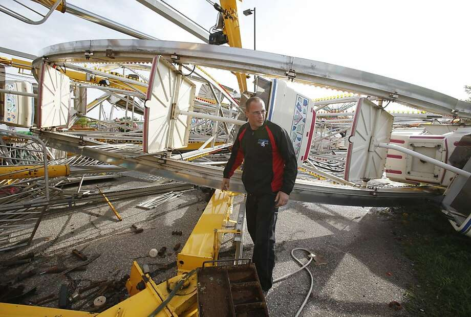 "Ottaway Amusement employee Chris Letterman walks around the Century Wheel in a parking lot near the corner of Kellogg and Greenwich in Wichita, Kansas, Sunday, April 15, 2012. The Ferris wheel and another ride toppled over on Saturday night during the tornado outbreak. ""You're looking at 2 million dollar, squished,"" Letterman said. (AP Photo/The Wichita Eagle, Mike Hutmacher) Photo: Jaime Green, Associated Press"