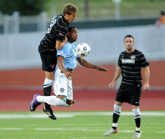 The San Antonio Scorpions' Fabian Kling (13) collides with the Puerto Rico Islanders' Nicholas Addlery (blue jersey) during the Scorpions' home opener of their inaugural season in the North American Soccer League (NASL) on April 15, 2012 at Heroes Stadium. Photo: John Albright, For The Express-News