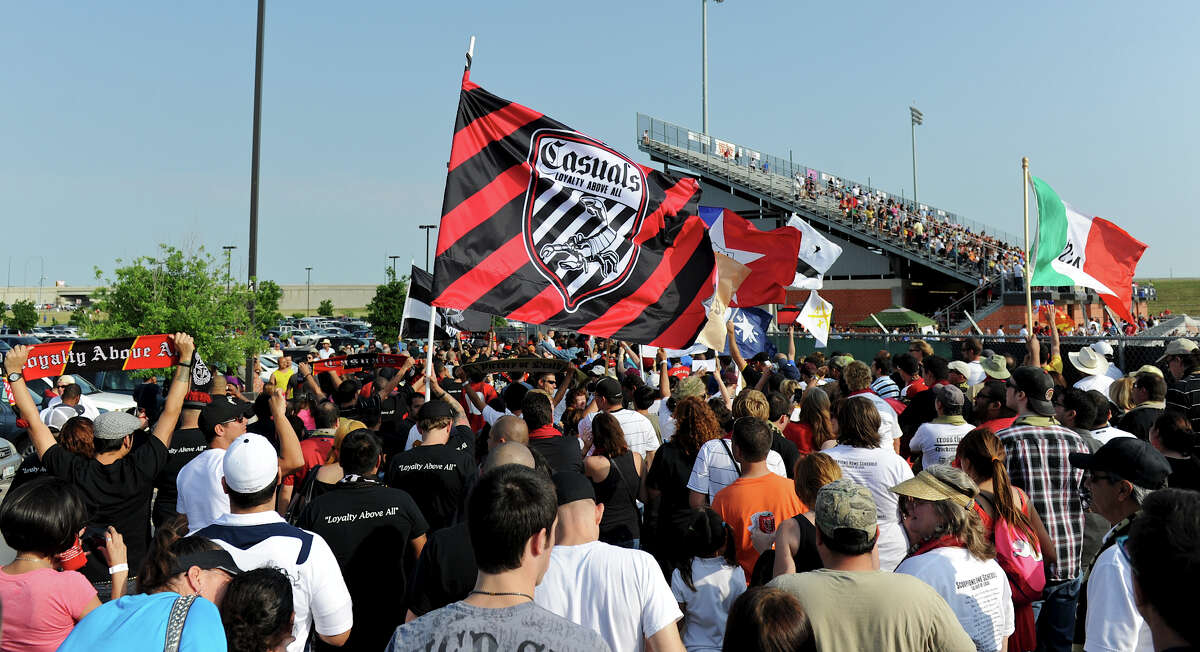 San Antonio Scorpions fans wave flags as they file into the stadium before the Scorpions' home opener of their inaugural season in the North American Soccer League (NASL) on Sunday, April 15, 2012 at Heroes Stadium.