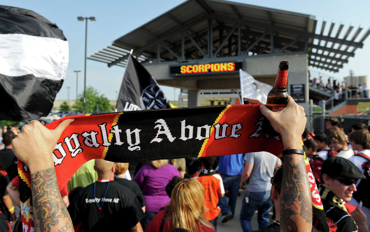 A San Antonio Scorpions fan holds up his scarf as he waits to enter the stadium before the Scorpions' home opener of their inaugural season in the North American Soccer League (NASL) on Sunday, April 15, 2012 at Heroes Stadium.