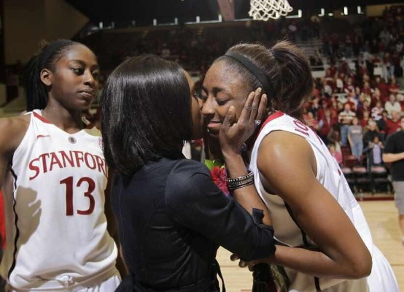 Stanford forward Nnemkadi Ogwumike, right, gets a kiss from her mother, Ify Ogwumike, center, as her