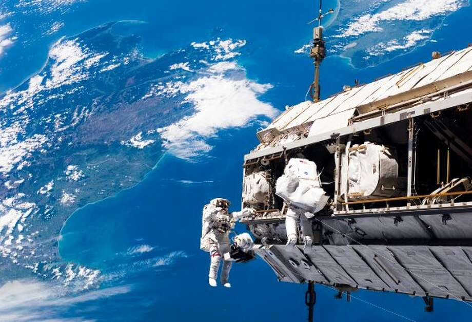 Backdropped by New Zealand and Cook Strait in the Pacific Ocean, astronaut Robert L. Curbeam Jr. (left) and European Space Agency astronaut Christer Fuglesang, both STS-116 mission specialists, participate in a spacewalk. (  / NASA)