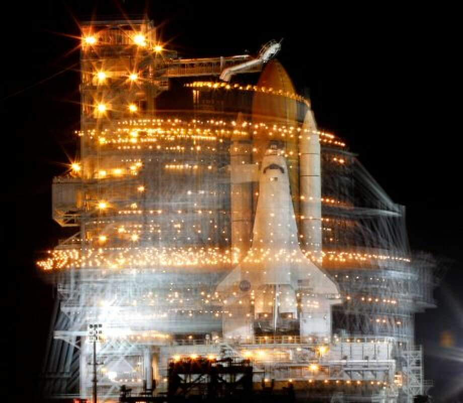 Atlantis is visible during a time exposure ahead of mission STS-122. The Rotating Service Structure is a blur as it rolls back to allow for filling the external fuel tank. The shuttle launched Feb. 7, 2008.  (Steve Ueckert / Chronicle)