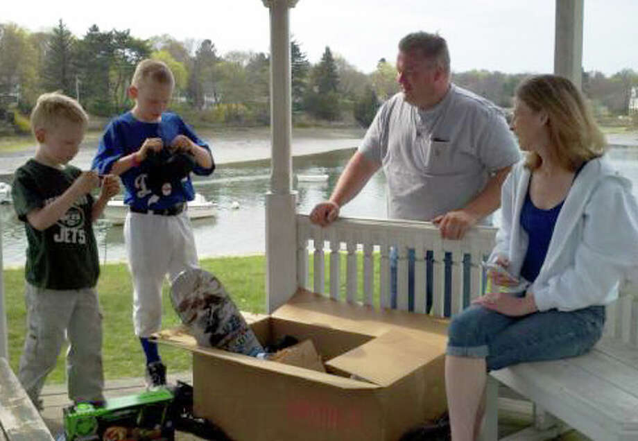 A local family looks through their won goodies at Pinkney Park in Rowayton. They found the box during Tony Hawk's Twitter Hunt. Photo: Contributed Photo