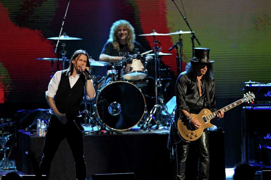 Guns N' Roses' Slash, right, and Steven Adler on drums, perform with singer Myles Kennedy, left, after induction into the Rock and Roll Hall of Fame Sunday, April 15, 2012, in Cleveland. (AP Photo/Tony Dejak) Photo: Tony Dejak, Associated Press / AP