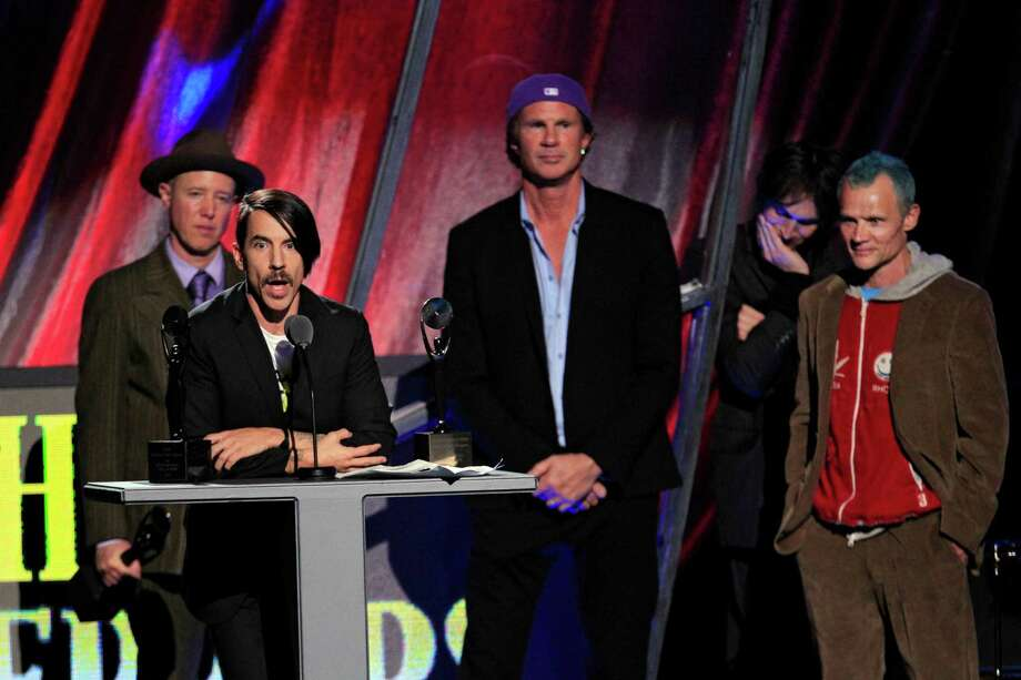 """Red Hot Chili Peppers' Anthony Kiedis speaks after induction into the Rock and Roll Hall of Fame Sunday, April 15, 2012, in Cleveland. Former member Jack Irons, back left, join Chad Smith, second from right, and Mike """"Flea"""" Balazary, right, onstage.  (AP Photo/Tony Dejak) Photo: Tony Dejak, Associated Press / AP"""