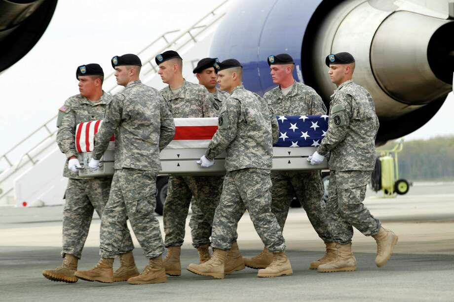 An Army carry team carries the transfer case containing the remains of Army Spc. Philip C. S. Schiller of The Colony, Texas, upon arrival at Dover Air Force Base, Del. on Saturday, April 14,  2012. The Department of Defense announced the death of  Schiller who was supporting Operation Enduring Freedom in Afghanistan. ( AP Photo/Jose Luis Magana) Photo: Jose Luis Magana, Associated Press / FR159526 AP