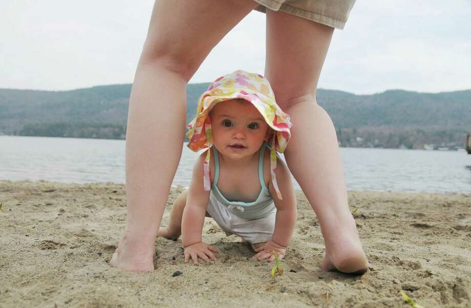 Spring McNiell of Lake George bends down to grab her daughter, Paisley Post, 10 months old,  as she crawled between her legs on the town beach on Monday, April 16, 2012 in Lake George, NY.  (Paul Buckowski / Times Union) Photo: Paul Buckowski