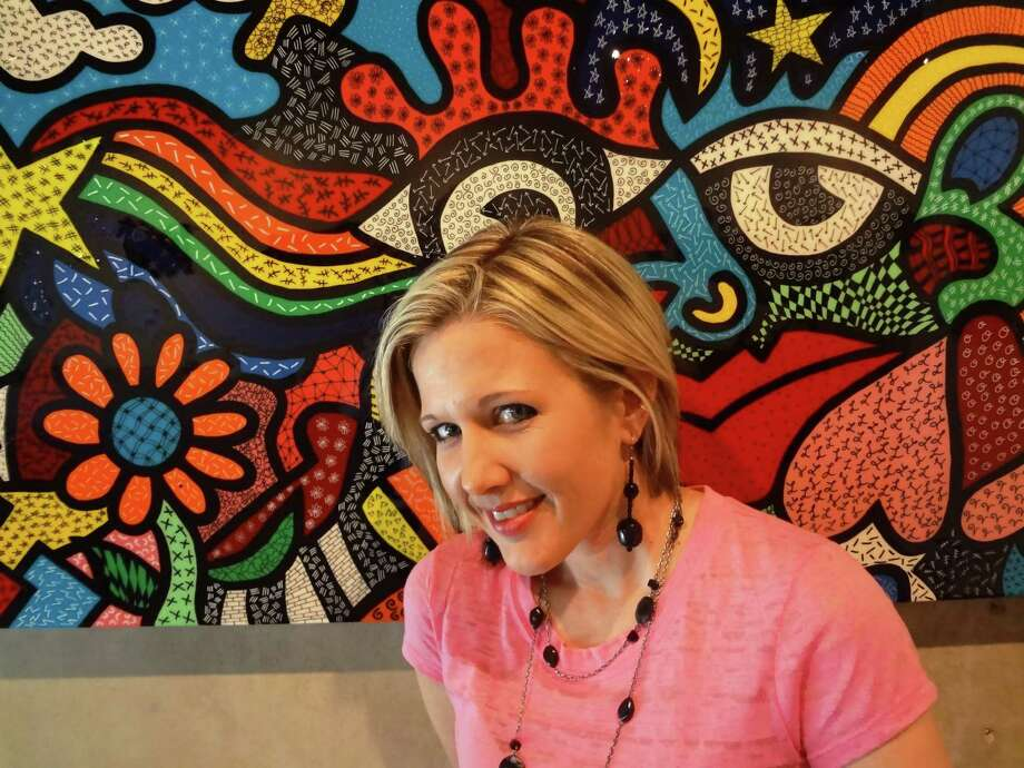 "Austin-based artist Allison Gregory is ""a color freak,"" as a viewer can tell from paintings such as ""Happiness Happening"" behind her. Photo: Steve Bennett, San Antonio Express-News"