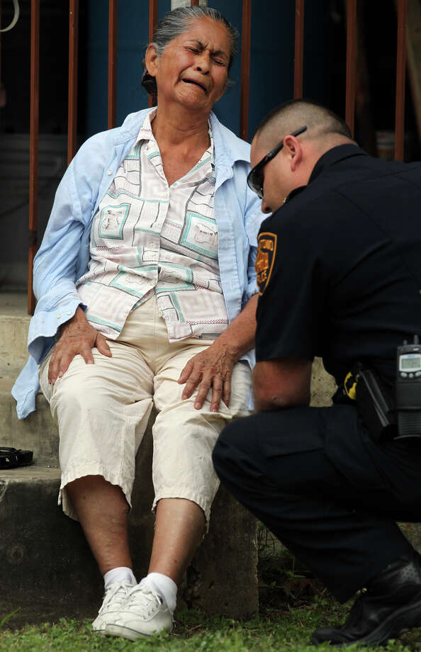 A San Antonio officer comforts a woman described by police as the wife of a man who was killed  while apparently using a brush cutter on Monday, April 16, 2012. Photo: JOHN DAVENPORT, SAN ANTONIO EXPRESS-NEWS