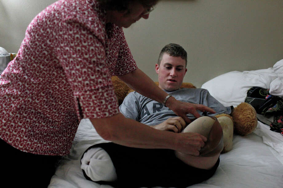 Army Pfc. Kevin asks his mother, Saralee Trimble, to put a shrinker on his leg quickly as he is in more pain from his recent surgery as she helps him get ready for the day in the small room they share at Powless Guest House at Fort Sam Houston in San Antonio on Wednesday, March 7, 2012. Photo: Lisa Krantz, San Antonio Express-News / @San Antonio Express-News