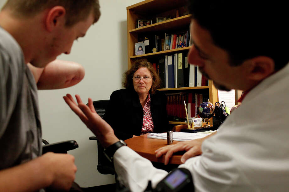Saralee Trimble watches as her son, Army Pfc. Kevin Trimble, 19, is seen by Dr. Raul Marin, right, at the Center for the Intrepid at Brooke Army Medical Center on Wednesday, March 7, 2012. Photo: Lisa Krantz, San Antonio Express-News / @San Antonio Express-News