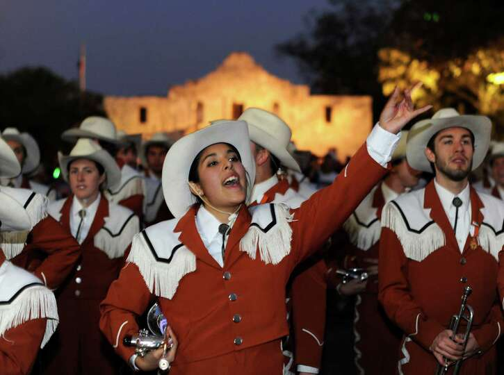 Ashley Trevino of the UT Longhorn Band cheers before the Alamo during the Fiesta Flambeau Parade on