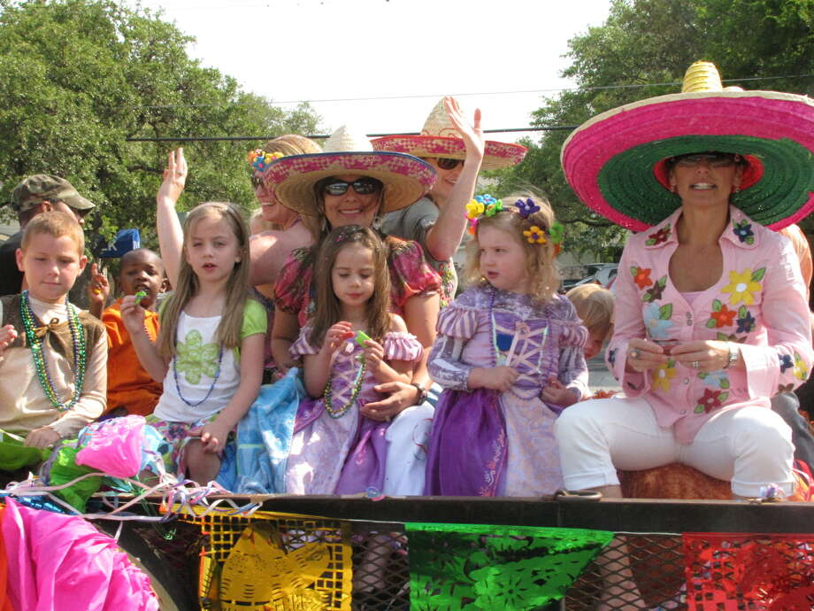 Parade riders on the Castle Hills Homeowners Association flatbed float wave to onlookers along Northwest Military Highway, kicking off the 2011 Fiesta Castle Hills. Photo: North Central News File Photo