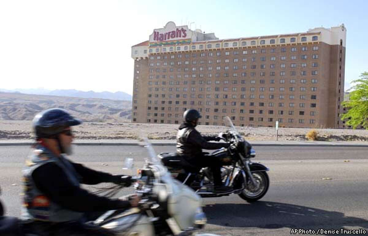 Two motorcyclists drive by Harrah's in Laughlin, Nev., the scene of a shooting between rival motorcycle gangs that left three people dead, Saturday, April 27, 2002, police said. (AP Photo/Denise Truscello)