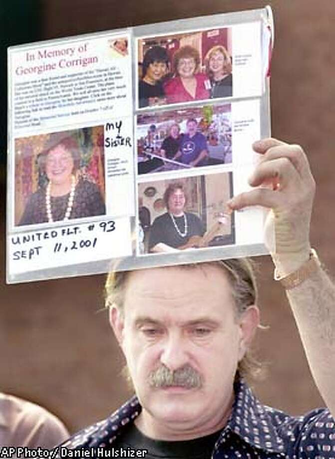"Kevin Marisay of Teaneck, N.J. holds up a memorial poster for his sister, Georgine Corrigan of Hawaii, outside the Marriott Hotel in Princeton, N.J. Thursday, April 18, 2002. The FBI is playing the flight recorder tape at the hotel for family of crew members and passengers from Flight 93, which crashed into a field in rural western Pennsylvania in the terrorists' attacks Sept. 11. Marisay said he considers those aboard Flight 93 the""forgotten 40"" because of all the publicity the World Trade Center attacks has received.(AP Photo/Daniel Hulshizer) Photo: DANIEL HULSHIZER"