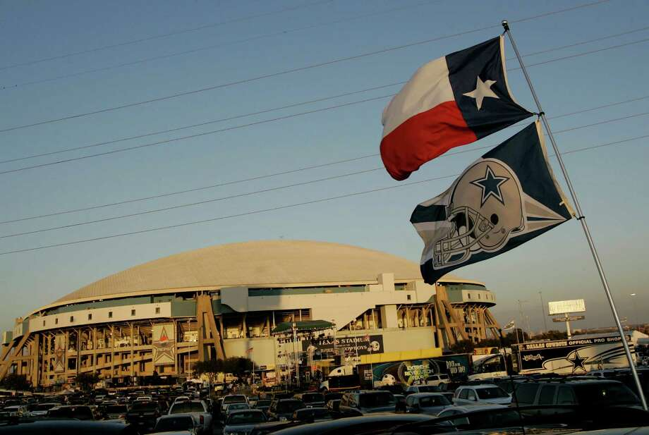 FILE - In this Dec. 14, 2008, file photo, a Texas state flag and a Dallas Cowboys banner flies over the parking lot at Texas Stadium before an NFL football game in Irving, Texas. Photo: Anonymous, AP / AP