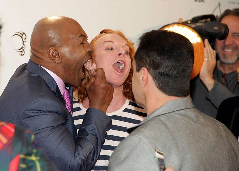 TOPSHOTS US fighting legend Mike Tyson (L) playfully bites the ear of US comedian Carrot Top (c) on