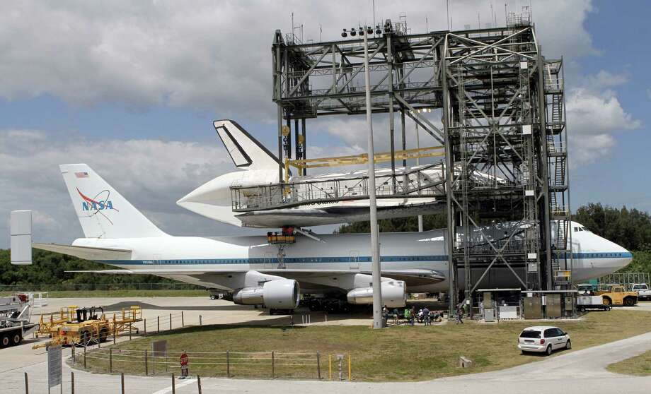 FILE - In this file photo provided by NASA, workers attach space shuttle Discovery to the Shuttle Carrier Aircraft in the mate-demate device at the Kennedy Space Center in Cape Canaveral, Fla., Sunday, April 15, 2012. Discovery will be transported to the Smithsonian National Air and Space Museum in Washington on Tuesday, April 17. (AP Photo/NASA, Kim Shiflett) Photo: Kim Shiflett / NASA