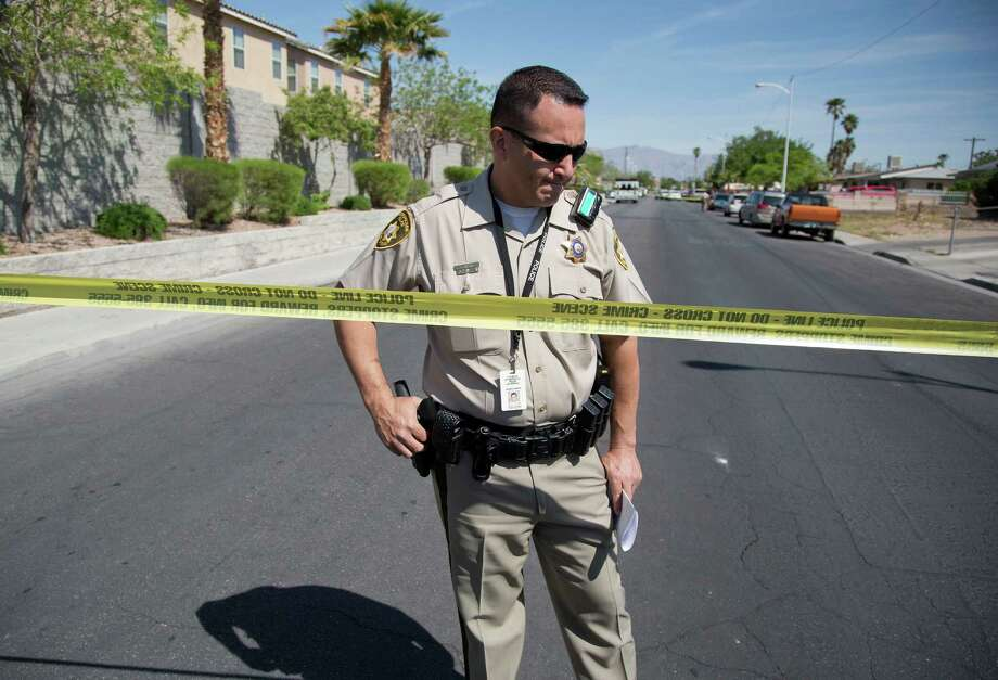 Las Vegas police officer Jacinto Rivera confirms the story a 9-year-old boy told at school on Monday: The bodies of the boy's mother and sister were inside a home. Photo: Julie Jacobson / Copyright 2012 The Associated Press. All rights reserved. This material may not be published, broadcast, rewritten or redistribu