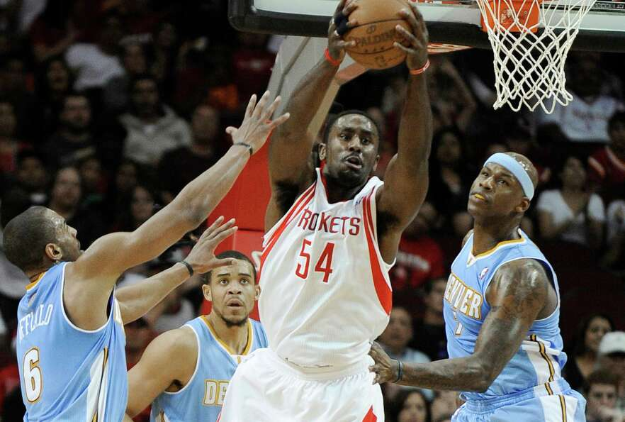 Houston Rocket Patrick Patterson grabs a rebound while surrounded by Denver Arron Afflalo, JaVale