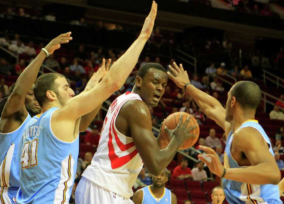 Houston Rockets center Samuel Dalembert, center, is crowded by  Denver Nuggets Kenneth Faried, left, Denver Nuggets center Kosta Koufos, center left, and Arron Afflalo, right, during the first half of a basketball game at the Toyota Center Monday, April 16, 2012, in Houston. The Nuggets won 105-102. Photo: Cody Duty, Houston Chronicle / © 2011 Houston Chronicle