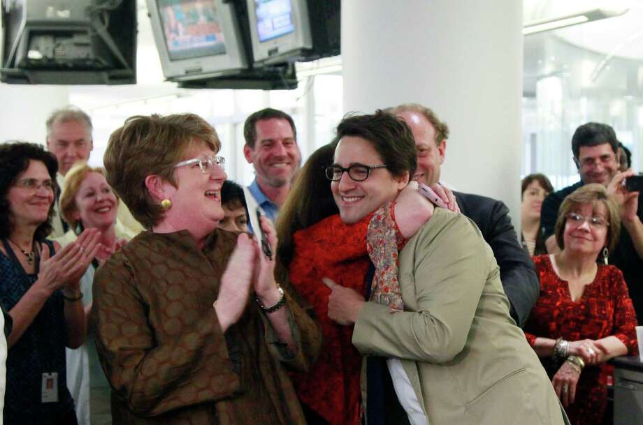Executive Associated Press Editor Kathleen Carroll, left, applauds as Associated Press reporter Adam Goldman, center, is hugged after winning the Pulitzer Prize for Investigative Reporting with three colleagues, Monday, April 16, 2012 in New York. They revealed a secret New York Police Department program that spied on Muslim neighborhoods. (AP Photo/Mark Lennihan) Photo: Mark Lennihan