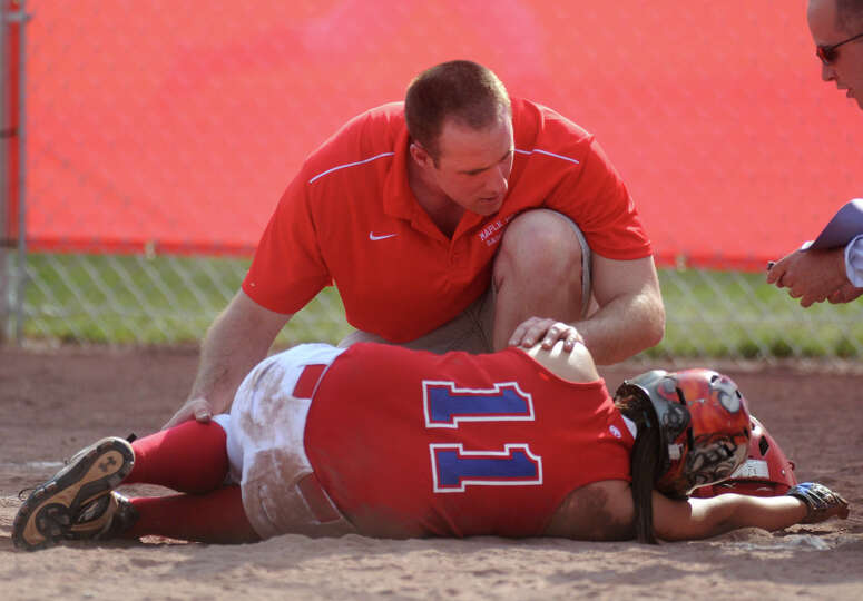Maple Hill coach Dave Austin tends to injured Sierra Pizzola after she slid into home during a softb