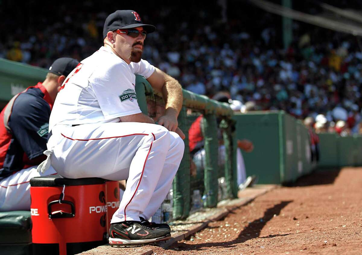 Boston Red Sox's Kevin Youkilis looks on from the top step of the dugout during Boston's 1-0 loss to the Tampa Bay Rays in a baseball game at Fenway Park in Boston Monday, April 16, 2012. Red Sox manager Bobby Valentine questioned Youkilis' commitment to the game in his weekly television interview, then apologized to the Boston third baseman on Monday. (AP Photo/Winslow Townson)