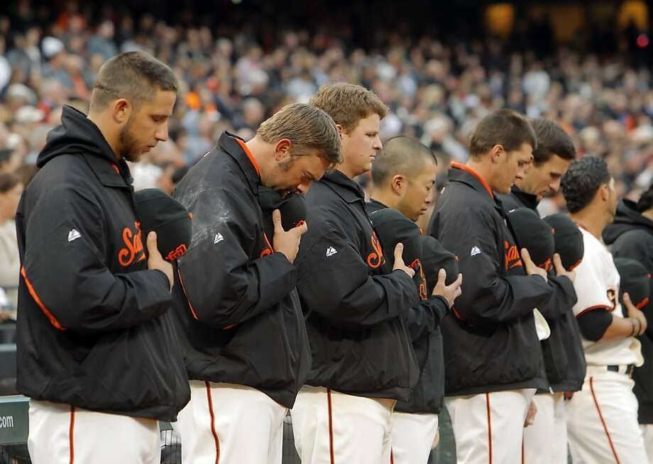 Giants team members bow their heads as the San Francisco Giants held a moment of silence  at AT&T Park in San Francisco, Calif., on Monday, April 16, 2012, for former ball girl Alexis Busch who died last weekend in a sailing accident off the Farallone Islands. Photo: Carlos Avila Gonzalez, The Chronicle