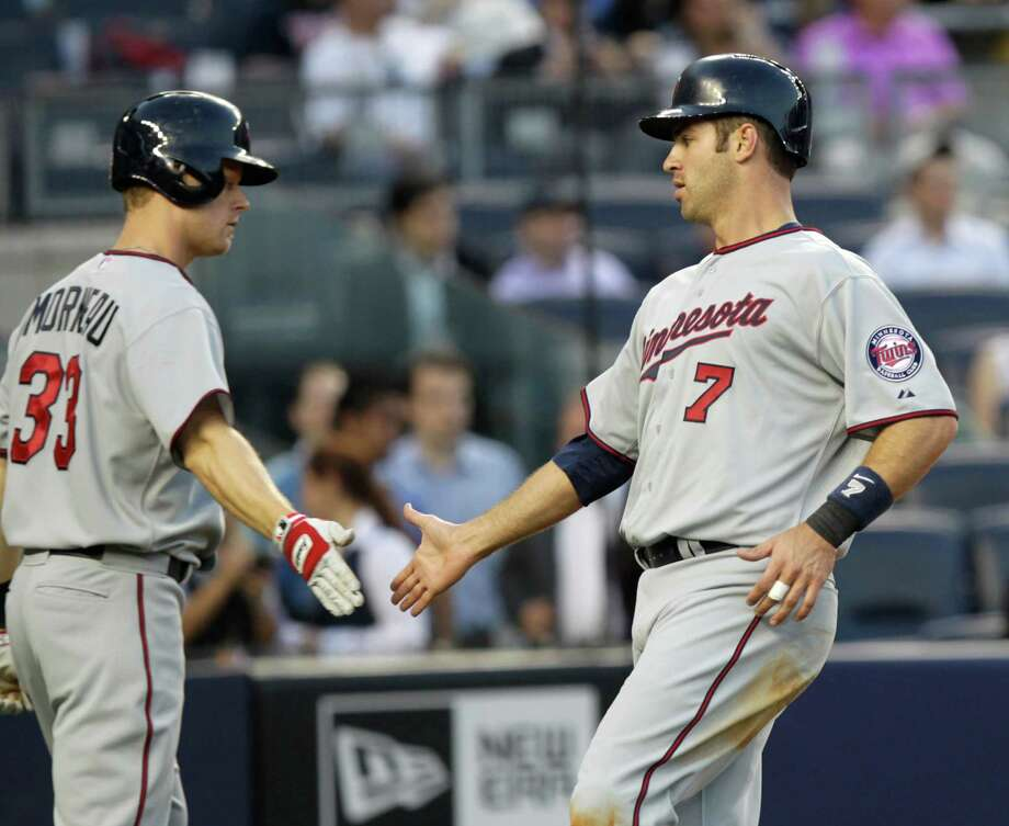 Minnesota Twins' Joe Mauer, right, is greeted by Justin Morneau after Mauer scored on a single by Josh Willingham during the first inning of a baseball game against the New York Yankees at Yankee Stadium in New York, Monday, April 16, 2012. Photo: AP