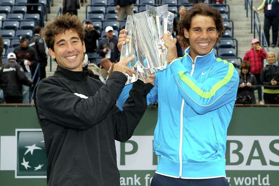 INDIAN WELLS, CA - MARCH 18:  Marc Lopez and Rafael Nadal of Spain pose for photographers after defeating Sam Querrey and John Isner during the doubles final of the BNP Paribas Open at the Indian Wells Tennis Garden on March 18, 2012 in Indian Wells, California.  (Photo by Matthew Stockman/Getty Images) Photo: Matthew Stockman / 2012 Getty Images