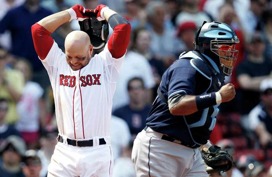 A game-ending strikeout leaves Cody Ross, left, infuriated by the umpiring but delights Rays catcher Jose Molina. Photo: Winslow Townson / FR170221 AP