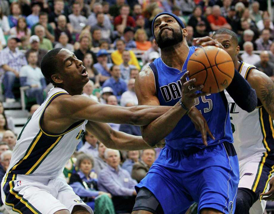 Utah's Alec Burks, left, fouls Dallas' Vince Carter during the first half of Monday night's game at Salt Lake City. The Jazz won 123-121 in triple overtime. Photo: Colin E. Braley / FR123678 AP