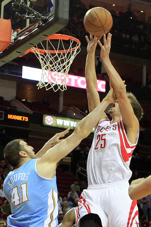 Nuggets center Kosta Koufos, left, sends a message to Rockets forward Chandler Parsons with a hard foul as Parsons tries to get an easy basket in the first half of Denver's win Monday night at Toyota Center. Photo: Cody Duty / © 2011 Houston Chronicle