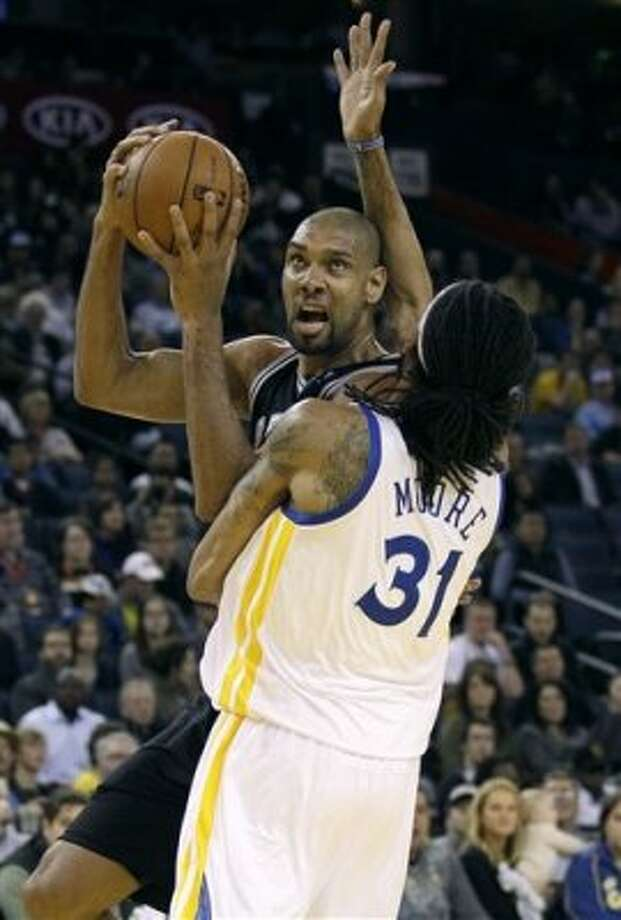 San Antonio Spurs center Tim Duncan, rear, looks for a shot against Golden State Warriors center Mikki Moore (31) during the first quarter of an NBA basketball game in Oakland, Calif., Monday, April 16, 2012. (AP Photo/Jeff Chiu) (AP)