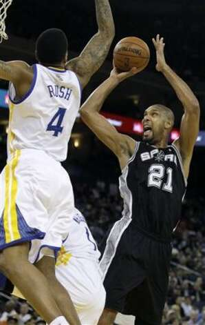 San Antonio Spurs center Tim Duncan (21) shoots against Golden State Warriors guard Brandon Rush (4) during the first quarter of an NBA basketball game in Oakland, Calif., Monday, April 16, 2012. (AP Photo/Jeff Chiu) (AP)