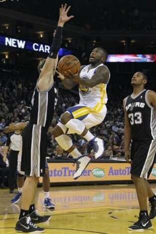 Golden State Warriors point guard Nate Robinson (2) shoots against San Antonio Spurs center Tiago Splitter (22), from Brazil, left, and power forward Boris Diaw (33) during the second quarter of an NBA basketball game in Oakland, Calif., Monday, April 16, 2012. The Spurs won 120-99. (AP Photo/Jeff Chiu) (AP)