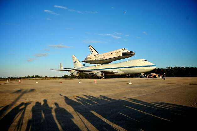 CAPE CANAVERAL, FL - APRIL 16:  Media watch as the space shuttle Discovery sits atop NASA's 747 Shuttle Carrier Aircraft (SCA) ready to transport it from Kennedy Space Center to the Washington D.C., on April 16, 2012 in Cape Canaveral, Florida.  Following the retirement of the shuttle fleet, Discovery will fly on Tuesday, April 17th to Washington for display at the Smithsonian's National Air and Space Museum.  (Photo by Roberto Gonzalez/Getty Images) Photo: Roberto Gonzalez, Getty Images