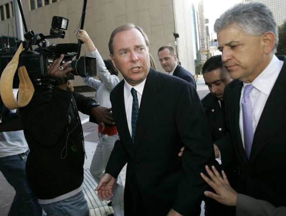 Former Enron CEO Jeff Skilling, left,  leaves the federal courthouse in 2006 with his attorney Daniel Petrocelli, right, after being sentenced to 292 months in federal prison. He later appeals the verdicts, hoping to get a new trial. (DAVID J. PHILLIP / AP)