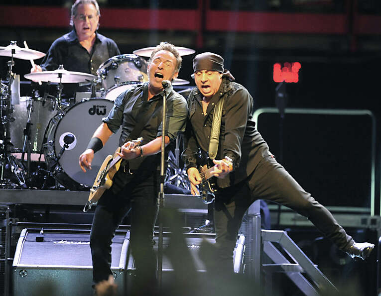 Bruce Springsteen sings with Steve Van Zandt while Max Weinberg plays drums at a sold out performanc