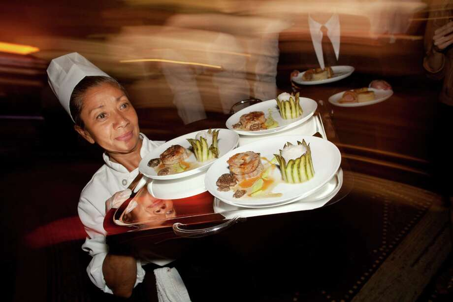 A tray of dishes are delivered to the dining room during the 2012 Grands Chefs Dinner, Monday, April 16, 2012, in New York. More than 40 world-renowned chefs converged in Manhattan's Gotham Hall to present their gastronomic creations. Photo: John Minchillo, AP / AP